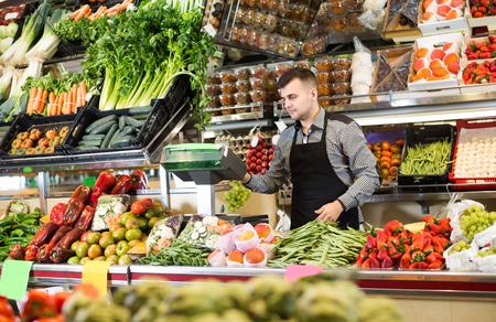 Il giovane venditore maschio sta pesando l'uva in negozio di alimentari.