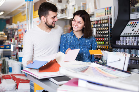 home improvement store: Young smiling couple examining color scheme in paint supplies shop