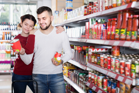 clase media: Smiling family buying tinned food at supermarket