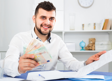 Young happy cheerful positive man struggling to pay utility bills and rent for his apartment