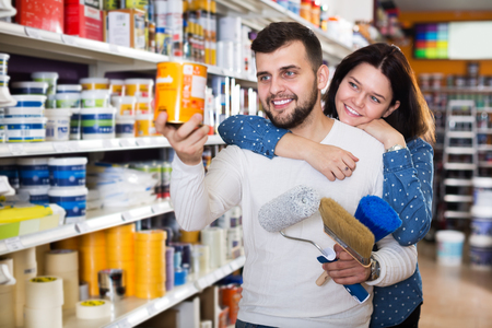 coatings: Young positive couple choosing materials for house decoration in paint supplies store