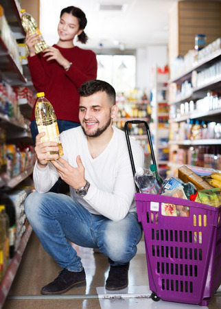Positive family reading lable of olive oil bottle at supermarket