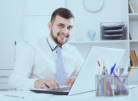 expertize: Positive man manager working effectively on project in office Stock Photo