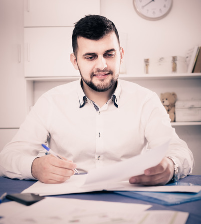 autograph: Smiling male signing  papers about financial agreement at home