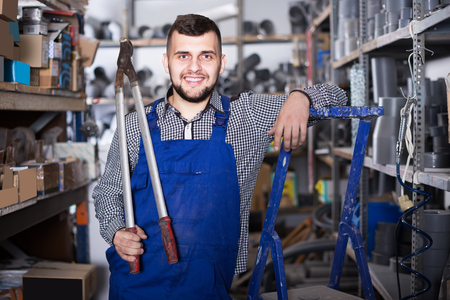 Smiling builder with pleasure showing his workplace in workshop Stock Photo