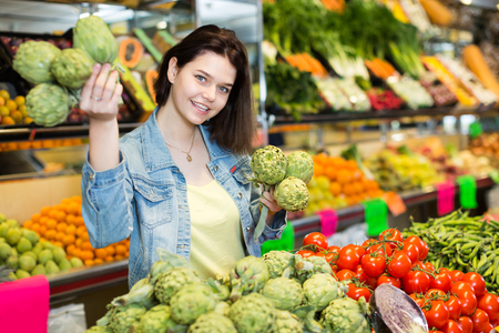 nourishing: Young female customer examining various fruits in grocery shop