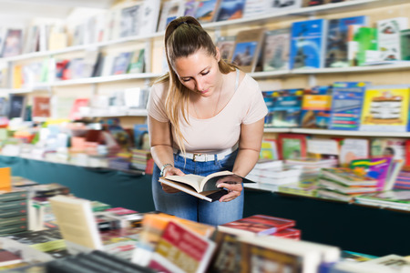 publishers: Ordinary woman buying books in hard cover in bookstore
