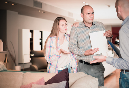 furor: Friendly family couple dissatisfied with service in furniture store Stock Photo