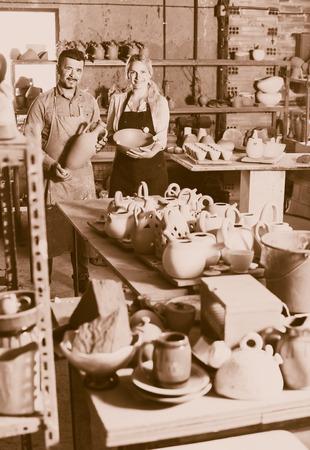 workroom: Two joyful artisans in aprons holding ceramics in hands in ceramics workshop