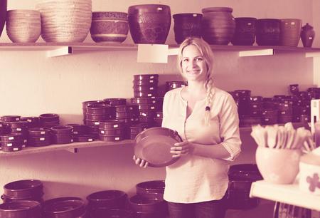 workroom: female customer choosing ceramics in ceramics workshop Stock Photo