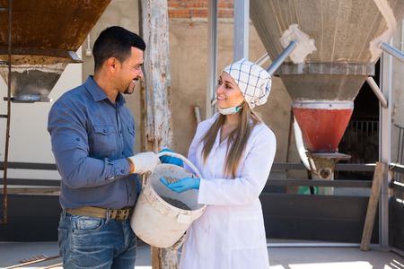 advice: Friendly smiling mature farmer and woman in white coat holding bucket with pelleted food for hogs