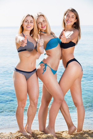 Portrait of three cheerful young women in swimsuits on  beach