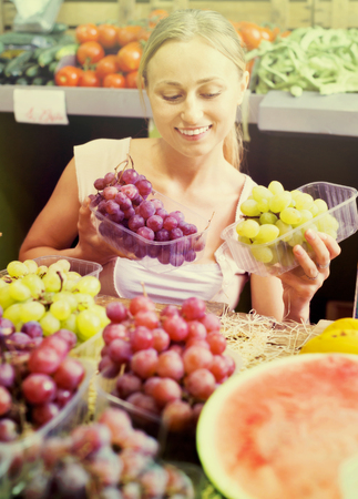 Cheerful young woman customer buying sweet ripe grapes on marketplace Stock Photo