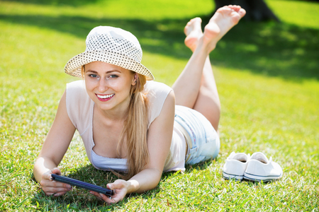 Smiling young happy barefoot woman lying on green grass in park and holding mobile phone in hands