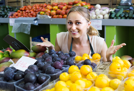 woman in apron holding ripe plums in hands in fruit store Stock Photo