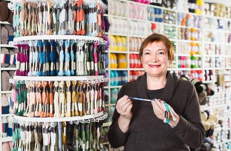 Weibliche Kundin kauft bunte Moulinefäden für ihr Hobby.