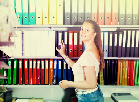 choise: Customer is choosing folders on the shelves in stationery store. Stock Photo