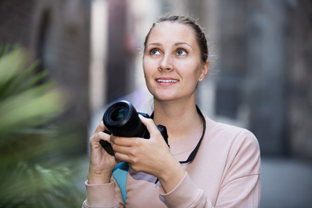 northern european: Young girl holding camera in hands and photographing at city Stock Photo