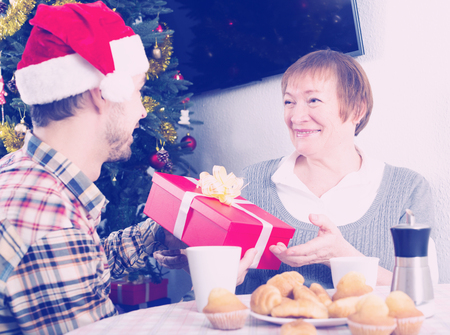 familia animada: Adult son and mother presenting gifts during Christmas at home