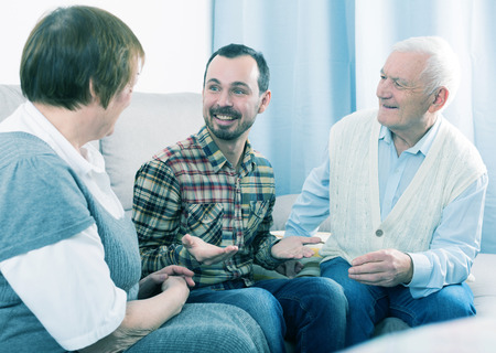 entertaining: Parents and adult son enjoying quiet evening together at home