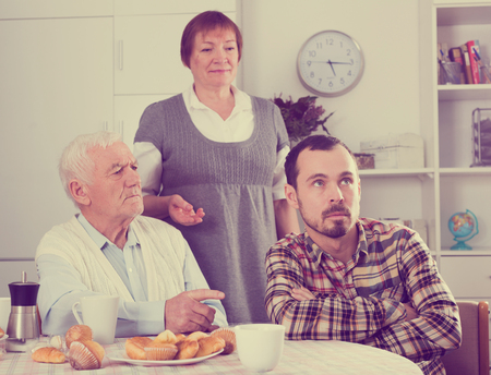 indicate: Elderly grandfather teaches his grandson in presence of grandmother Stock Photo
