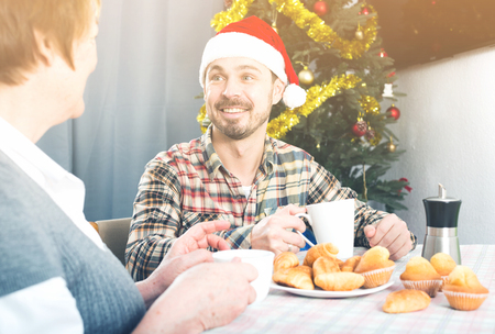 christmas spending: Smiling mother and adult son spending Christmas together at home Stock Photo
