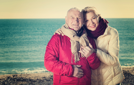 coldness: Mature man and woman walking by sea on sunny day Stock Photo