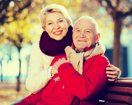 coldness: Mature man and woman sitting comfortably on bench in park