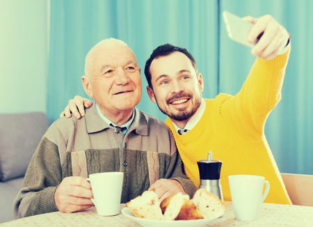eldest: Elderly father and his son make selfie at home for breakfast
