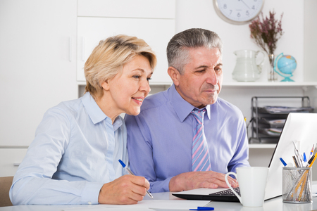 compile: Mature employees working on project together on computer at office
