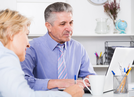 execute: Mature head gives task to assistant at office at table