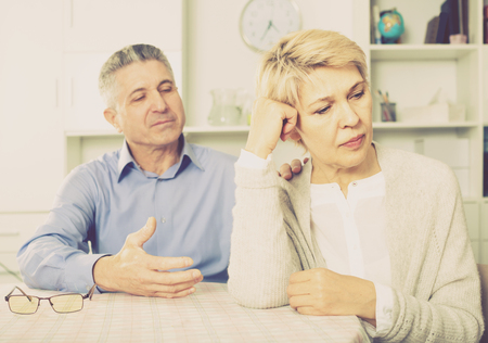 mature husband and wife arguing with each other and try to resolve family conflict at table