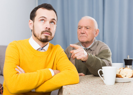 Elderly father talking seriously and instructs his son at home Stock Photo