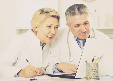 Mature doctor and nurse examine patient data in hospital computer database Stock Photo