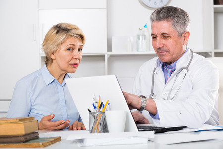 Mature woman visits doctor in hospital for survey and check of your health Stock Photo