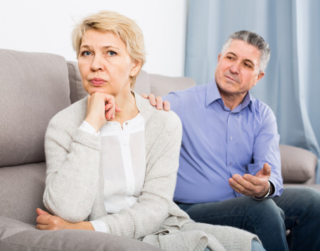 middle-aged couple quarreling at home with each other and take offense