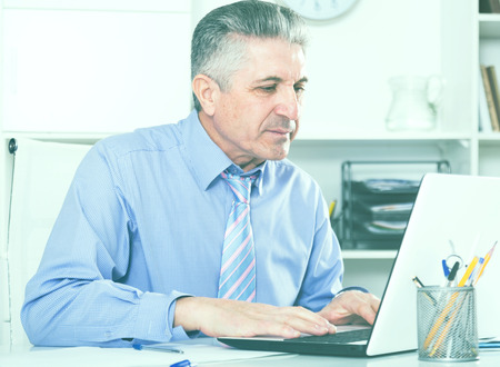 governed: Mature lawyer preparing important documents on computer at legal consultation office Stock Photo