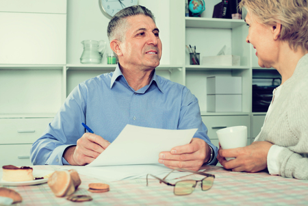 queries: happy mature couple at table attentively study documents and sign agreement