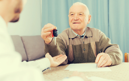 eldest: Elderly man and young man sign contract car rent and hand over keys