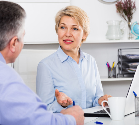 Male and female business partners discussing documents deal Stock Photo