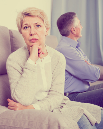 reluctance: sorry middle-aged couple quarreling at home with each other and take offense