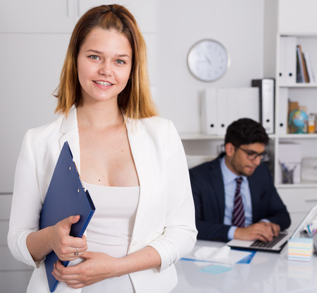 Businesswoman ready to work standing in office with male colleague behind