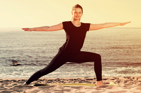 athleticism: Adult woman in black T-shirt is practicing yoga on the beach. Stock Photo