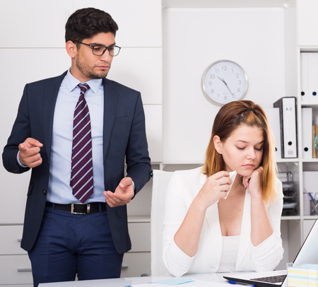 25s: Dissatisfied manager scolding frustrated female assistant in office Stock Photo