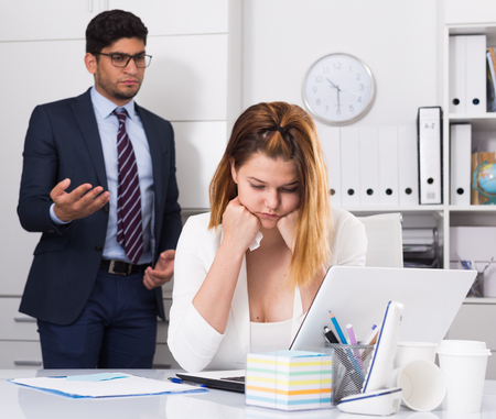 25s: Upset woman sitting at laptop in office with disgruntled boss behind