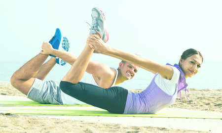Positive guy and young woman doing workout on beach by sea