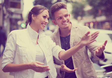sidewalk talk: Positive woman showing direction to guy at the street