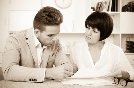 Cheerful young man and mature woman sit at table and discuss legal aspects of paperwork
