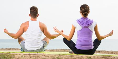 Cross-legged american couple practice yoga on beach in morning
