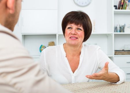 Employer discusses with elderly woman term of contract Stock Photo